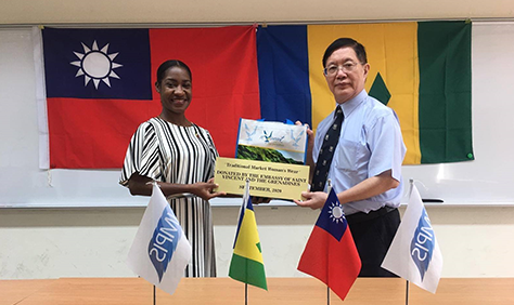 Counsellor Ms. Shebby-Ann Dennie from Embassy of St. Vincent and the Grenadines gifting the traditional outfit to Program Director of IMPIS, Professor Chung-Chian Teng.